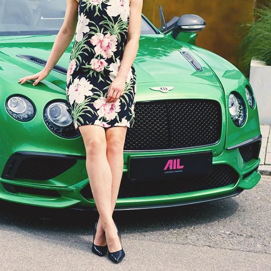 Frau an grünem Bentley angelehnt